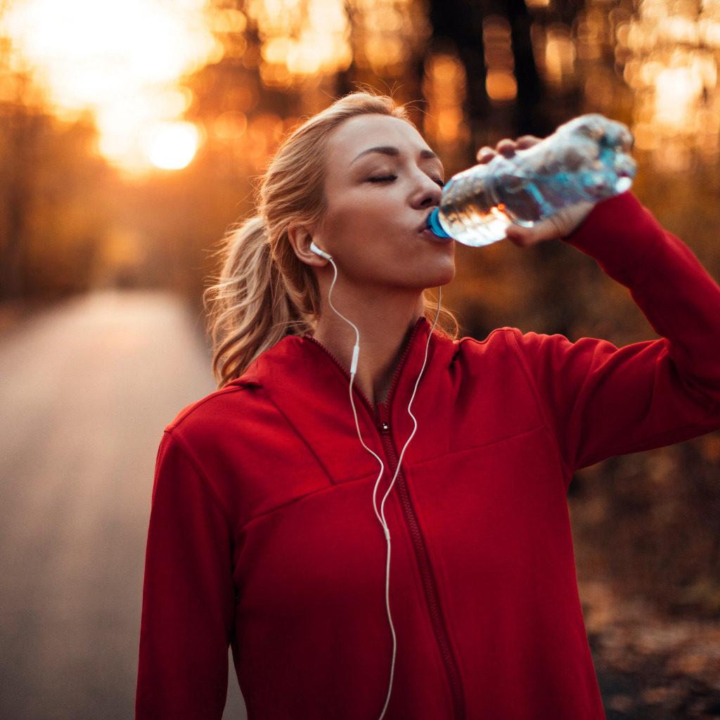 Frau trinkt Wasser beim Joggen