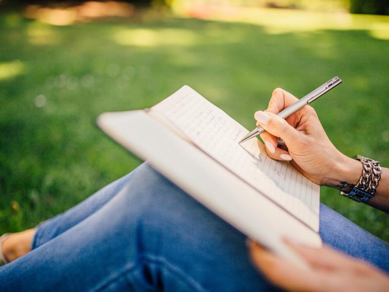 Frau schreibt in ein Erfolgstagebuch