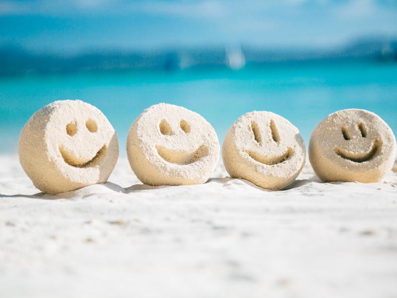 Smileys im Sand zeigen Spaß beim Sport