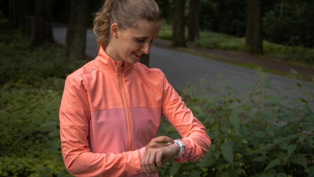 Läuferin schaut auf ihre Pulsuhr